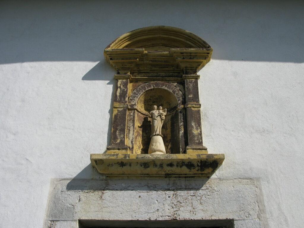 Madonna mit Kind über dem Seiteneingang der Pfarrkirche.  | © Christian von Arx