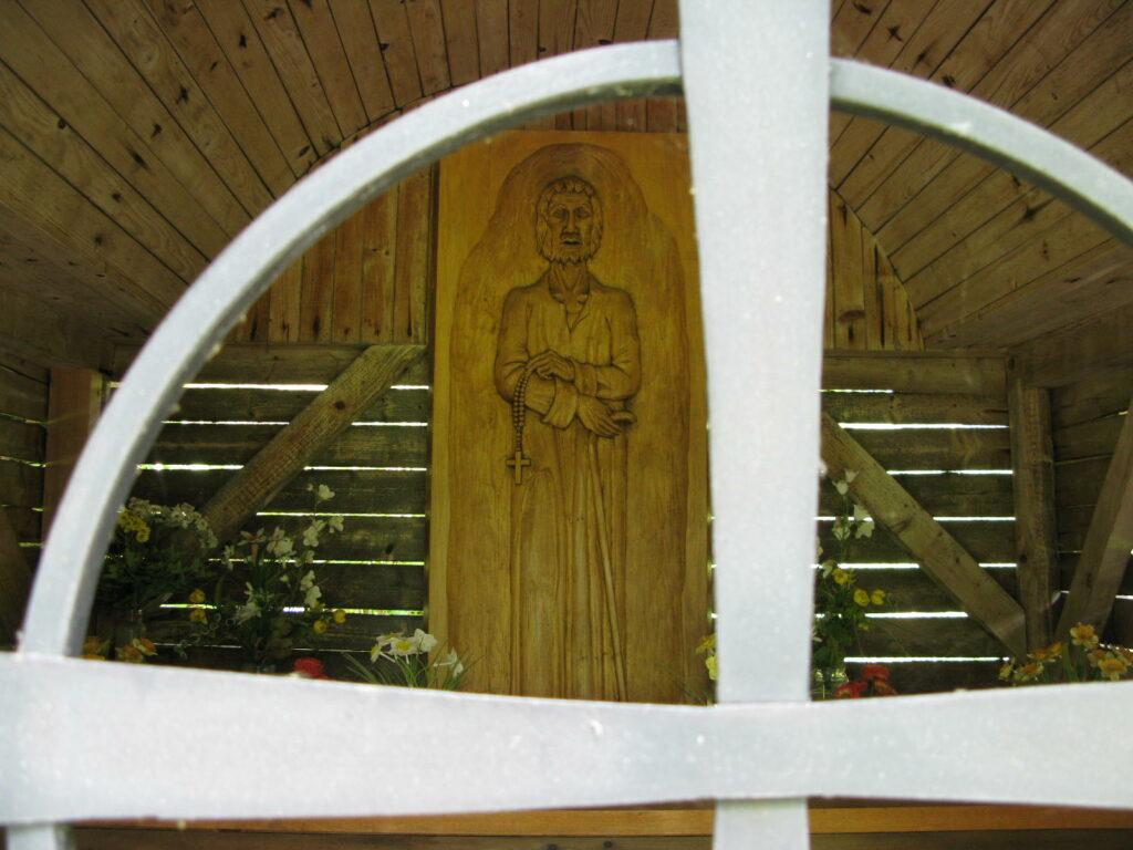 Blick durch das als Kreuz gestaltete Gitter des Oratoire St-Nicolas auf die geschnitzte Darstellung von Bruder Klaus.  | © Christian von Arx