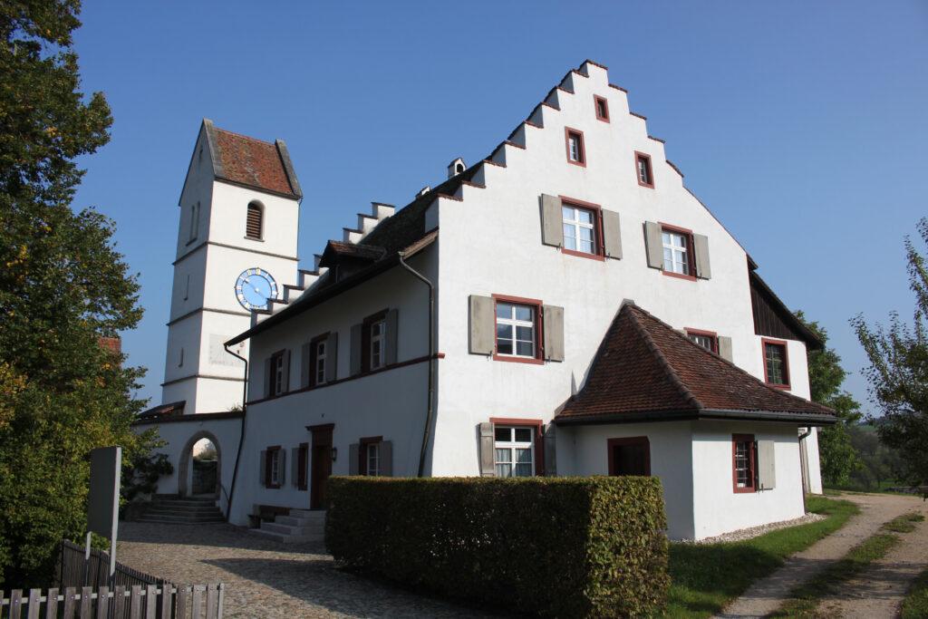 Die refomierte Kirche St. Niklaus in Oltingen bildet zusammen mit dem Pfarrhaus und weiteren Gebäuden ein eindrückliches Ensemble. | © wikimedia/Roland Zumbuehl