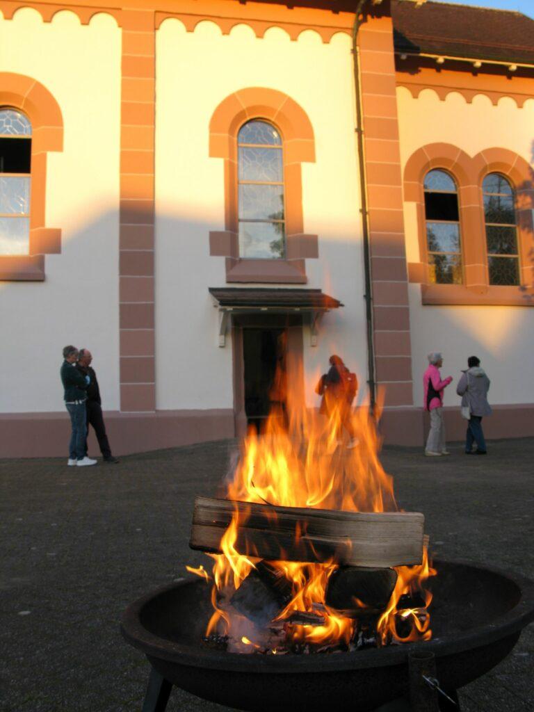 Sissach: Hier lodert das Feuer vor der Kirche noch im Abendlicht, später erzählte Diakon Martin Tanner hier biblische Geschichten.  | © Christian von Arx