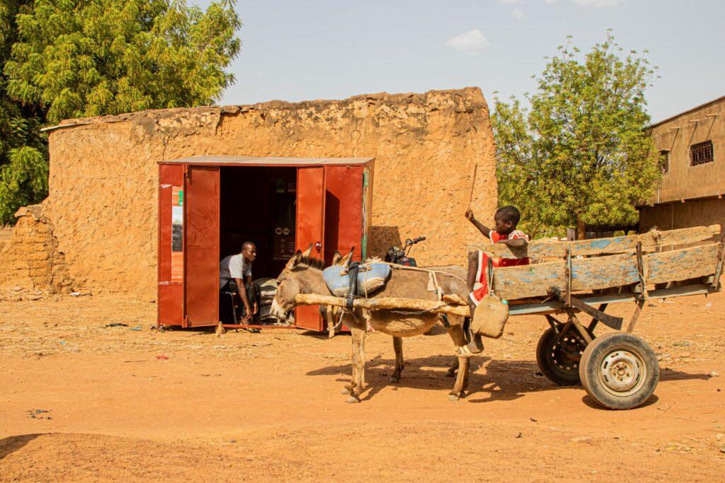 Im kleinen Laden von Seybou Diarra erhalten die örtlichen Bäuerinnen und Bauern auch Beratung, welche Nährstoffe die Bio-Dünger enthalten.   © John Kalapo/Caritas Schweiz